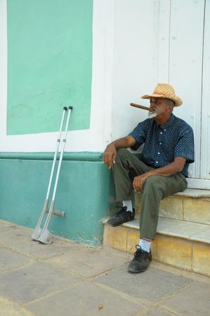 hombre fumando puro: TRINIDAD, CUBA - 26 de mayo 2013 el hombre de fumar cigarros locales cubana y posando para las fotos mientras se est� sentado en la calle en la UNESCO protegida de la ciudad de Trinidad, Cuba.