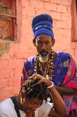 african ancestry: HAVANA, CUBA - JANUARY 20, 2013 Afro-Cuban man doing dreadlock hair to another Cuban man on street in Havana, Cuba. In Cuba around 20 per cent population have African genetic ancestry.