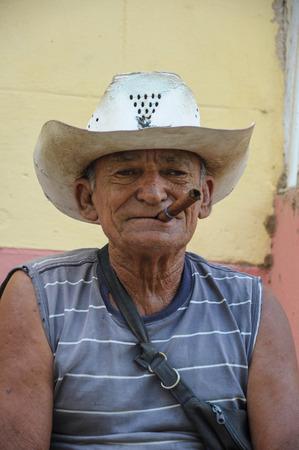 hombre fumando puro: TRINIDAD, CUBA - 28 de enero 2013 de fumar cigarros hombre local de Cuba y posando para las fotos mientras se est� sentado en la calle en la UNESCO protegida de la ciudad de Trinidad, Cuba.