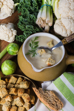 rustic kitchen: cauliflower soup on rustic kitchen table Stock Photo