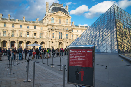 PARIS, FRANCE -  NOVEMBER 9, 2014 Pickpocket beware sign on front of the  queuing people to Louvre museum in Paris, France