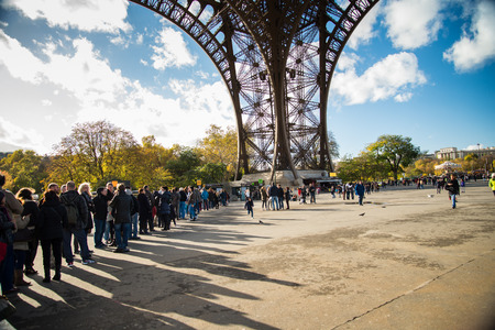 atraction: PARIS, FRANCE - NOVEMBER 11, 2014 People, mainly tourists queuing to get acces to Eiffel Tower , main tourist atraction in Paris, France.