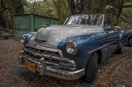 communists: HAVANA, CUBA - JANUARY 18, 2013 Classic American car park on street in Havana,Cuba.Cuba is known for the beauty of its vintage cars