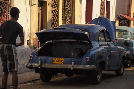 communists: HAVANA, CUBA - JANUARY 20, 2013 Classic American car park on street in Havana,Cuba.Cuba is known for the beauty of its vintage cars
