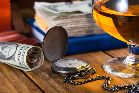 Wealthy man desk, cuban cigars dollar notes, vintage watch and alcohol photo