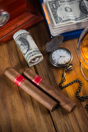 Top view, rich person or bussinesman desk with cuban cigar, bank notes and rum photo