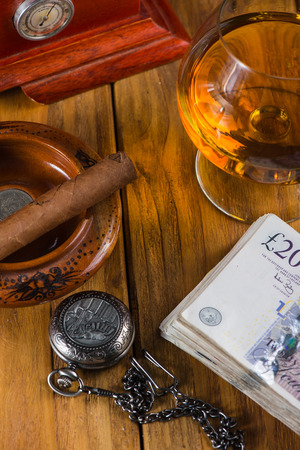 alcochol: Wealthy man desk, cuban cigars sterling notes, vintage watch and alcochol Stock Photo