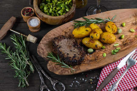 rustic kitchen: Beef steak with roasted potatoes in rustic kitchen