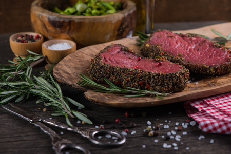 peppered: Peppered beef steak with herbs in vintage kitchen Stock Photo