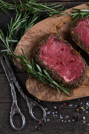peppered: Raw peppered steak with herbs on wooden table
