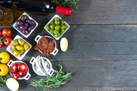 spanish food: selection of spanish tapas with red wine from above