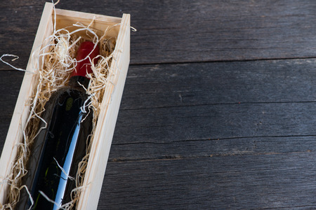 Red wine bottle in wooden case with straw on rustic background photo