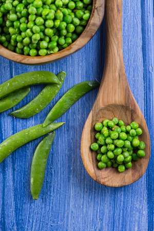 wooden spoon with fresh peas and whole beans on rustic table photo