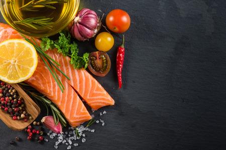 Gedeelte van verse zalm met specerijen, kruiden en fruit op een zwarte achtergrond leisteen Stockfoto