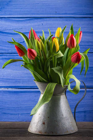 FResh spring bunch of tulips in vintage rusty vase photo