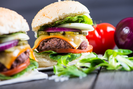 fast meal: traditional pub style burger  on wooden table Stock Photo