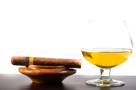 Cuban cigar and glass with rum or cognac isolated on wooden bar photo
