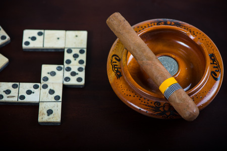 Cuban cigar in ash tray and domino photo