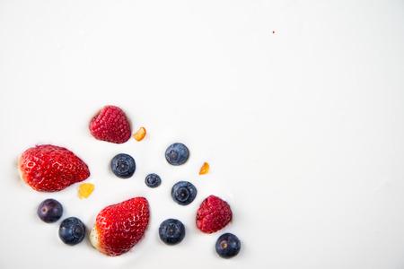 yogur: frutas bayas frescas aisladas en el yogur griego, fondo sano