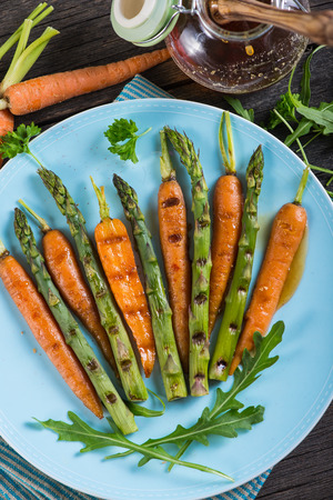 colorful spring healthy dish with grilled carrots and asparagus Фото со стока