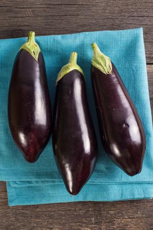aubergine: Vibrant fresh aubergine on rustic wooden table Stock Photo