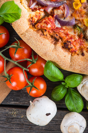 vegeterian: Fresh homemade vegeterian pizza with ingredients, overhead on wooden table Stock Photo