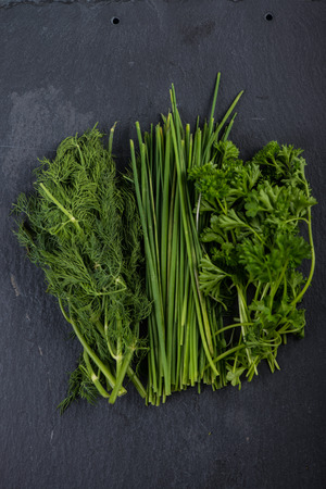 garden fresh: Spring garden fresh chives,parsley and dill on black slate  background