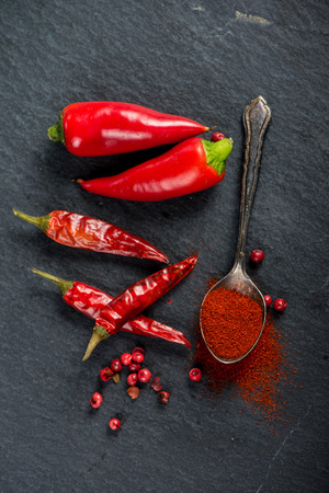 grounded: Vibrant red mexican hot chilli pepper, whole and grounded Stock Photo