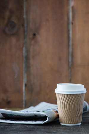 Take away coffee and newspaper on wooden background Banco de Imagens