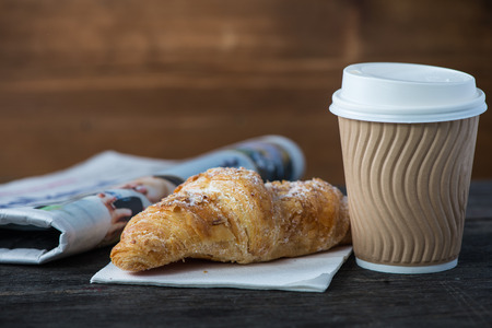 Take away coffee and fresh croissant and newspaper on wooden background