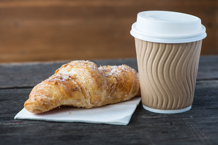 Take away coffee and fresh croissant on wooden background