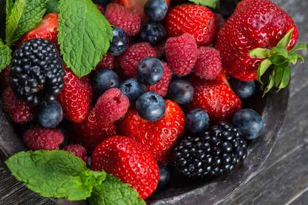 Fresh summer berries with mint in rustic bowl on wooden table Reklamní fotografie - 40543475