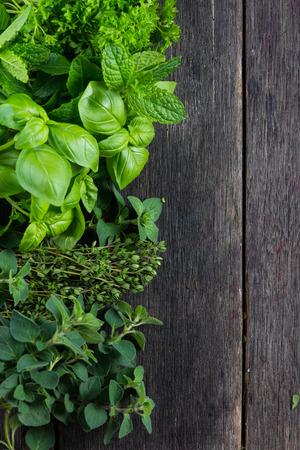 新鮮なハーブは、素朴な木製のテーブルの上の家の庭でカットします。