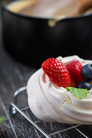 Homemade pavlova meringue with fresh berries on wooden rustic table photo
