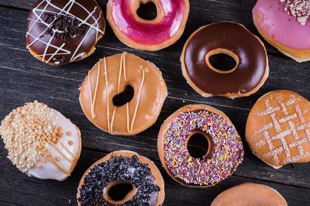 Hand versierde ambachtelijke donuts op houten rustieke tafel, van boven Stockfoto