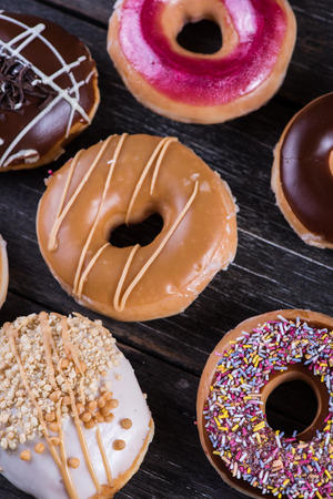 artisan bakery: Hand decorated artisan donuts on wooden rustic table, from above