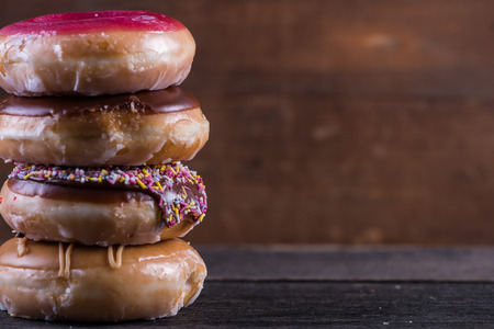 artisan bakery: Stack of hand decorated artisan donut, wooden background with copy space Stock Photo