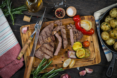 raw food: Medium rare grilled ribeye steak on wooden rustic cutting board