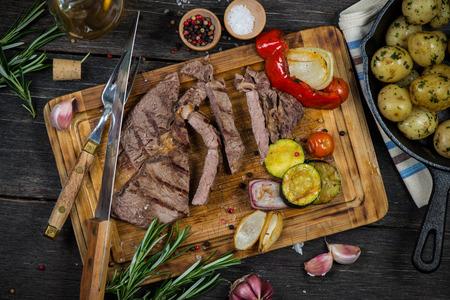 a rare: Medium rare grilled ribeye steak on wooden rustic cutting board