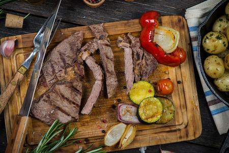 the medium: Medium rare grilled ribeye steak on wooden rustic cutting board