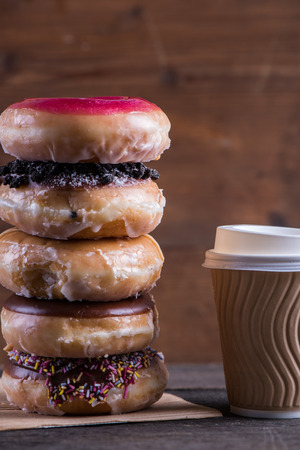 Stack of fresh artisan donuts and take away coffee on wooden