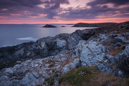 timelapse: Dramatic rocky cliffs at sunrise twilight in West Pentire Cornwall, motion blur