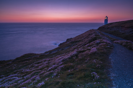 Trevose Head lighthouse on rocky cliffs in Cornwall, England at twilight