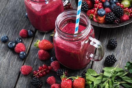 batidos de frutas: Bayas del verano smoothie en tarro de albañil en la mesa de madera rústica Foto de archivo