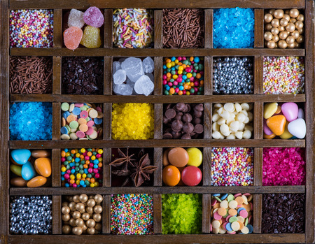 chocolate sprinkles: Vintage wooden box with sugar decoration, from above Stock Photo