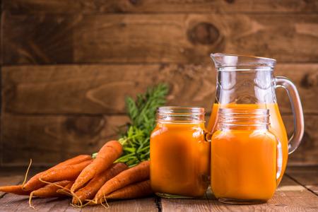 zanahoria: El jugo de zanahoria en el tarro de albañil en el fondo de madera, espacio de la copia Foto de archivo