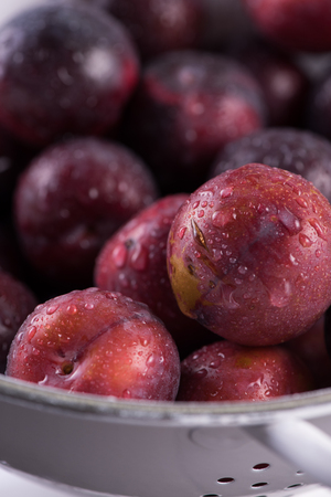 colander: Fresh plums in rustic colander on wooden table