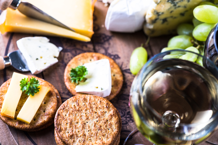 Cheese board selection with wine, on wooden rustic table