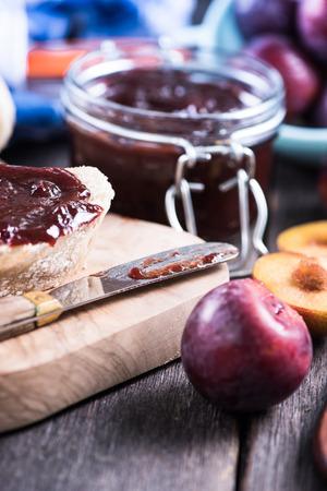 marmelade: Homemade organic plum marmelade with bread on wooden board