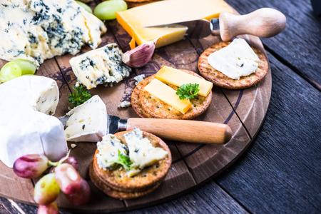 galletas integrales: Galletas de avena con selección de quesos a bordo de madera rústica Foto de archivo